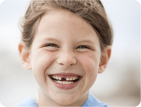 Close up of the Young Girl smiling with Missing Teeth