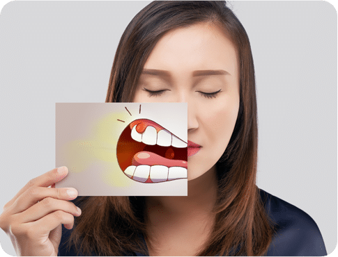 Asian Woman in dark blue shirt with closed eyes holding the card with bad breath illustration in front of her mouth